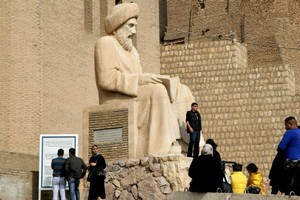 Tourists look at a statue of Kurdish writer Ibn al-Mustawfi at the entrance to the citadel in the northern Iraqi city of Arbil. Photo / AFP