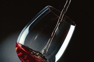close-up of red wine being poured into a glass