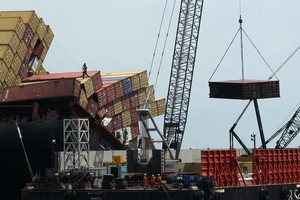 Salvors pictured standing on the fallen shipping containers onboard the Rena as other containers are lifted by the crane. Photo / Alan Gibson.