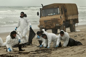 Army personnel clean up oil on Papamoa Beach. Photo / Alan Gibson