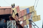 Salvors removing containers from the Rena, say the ship is trying to talk to them, asking for help. Photo / Getty Images
