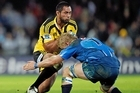 Serge Lilo of the Hurricanes is tackled by Dewald Potgieter of the Bulls. Photo / Getty Images
