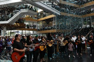 Guitarists serenade the separation as confetti rains down in the Telecom building yesterday. The companies have been operating at arm's length since 2008. Photo / Sarah Ivey