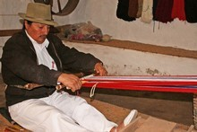 Rafael Cotacachi weaves a strip of cloth with his backstrap loom. Photo / Jim Eagles