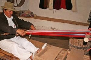 Rafael Cotacachi weaves a strip of cloth with his backstrap loom. Photo / Jim Eagles