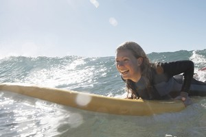 Getting fit is as easy as hopping on a board and catching waves. An hour's worth of surfing burns about 115 calories in a woman of average build and 125 in an average man. Photo / Thinkstock