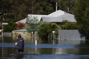 A local resident wades through flood waters from the Wimmera River in Dimboola, Australia. Many small towns in Victoria are ordering evacuations as water levels continue to rise, with peaks now expected later this week. Photo / Getty Images