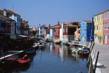 Brightly painted houses reflect in the peaceful canals of Venice's Burano Island. Photo / Paul Rush