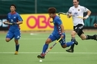 Hoon Suk Cho of Korea (C) takes the ball upfield during the match between Korea and Germany on day three of the 2011 Men's Champions Trophy at the North Harbour Hockey Stadium in Auckland. Photo / Getty Images