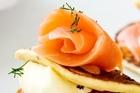 Salmon on potato pikelets, creme fraiche and dill. Photo / Babiche Martens