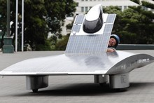Solar Fern driver Rob Glassey squeezes into the cockpit of the solar powered-car at Parliament, Wellington. Photo / Mark Mitchell