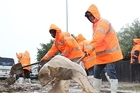 Workers shovel mud following Nelson's severe downpour. Photo / Andrew Board