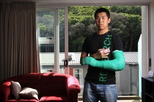Michael Tiang is couch bound over the Christmas break after falling through a glass ranch slider and badly cutting his arm and fingers. Photo / Greg Bowker