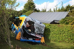 The North Star bus was firmly lodged up against the damaged wall of a house in Torbay after it veered off the road. Photo / Greg Bowker