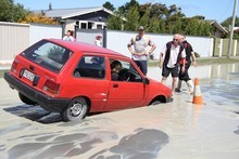 Residents try to free a car stuck in a liquefaction sink hole in Bower Avenue, Parklands, after today's quakes. Photo / Geoff Sloan