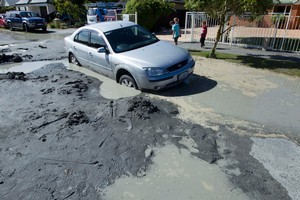 A car rests in sink hole caused by liquefaction in the Christchurch suburb of Parklands after a series of earthquakes struck Christchurch today. Photo / Simon Baker
