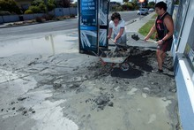 Leka Lafaele (right) and Mathew Cargill shovel liquefaction away from Mathew's mum's dairy in the Christchurch suburb of New Brighton after a series of earthquakes struck the city today. Photo / Geoff Sloan