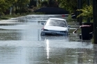 A car is swamped by flooding caused by liquefaction in the suburb of New Brighton after a series of earthquakes that struck Christchurch. Photo / Simon Baker