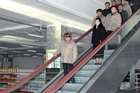 North Korean leader Kim Jong Il, left, rides an escalator as he visits a Pyongyang supermarket. The  people immediately behind him are his sister Kim Kyong Hui, his son Kim Jong Un. Photo / AP