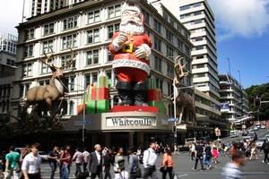 The giant Santa above Whitcoulls is one of very few Christmas decorations visible on Queen Street. Photo / Sarah Ivey