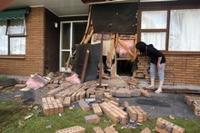 A car crashed into the home of 81-year-old Rollea Follick on Pownall Street in Masterton last night. Daughter Stella Usherwood looks at the damage to the bedroom wall. Photo / APN
