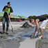 Daniel Marsh and Jason Myburgh clean up liquefaction from Chadbury Street. Photo / Geoff Sloan 