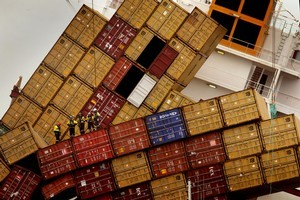 Salvors pictured standing on fallen shipping containers onboard the MV Rena. Photo / Alan Gibson