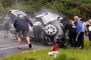 Bystanders and police officers do their best to prevent the wreckage of two vehicles catching fire after they collided on State Highway One at Otaihanga,between Paraparaumu and Waikanae on the Kapiti Coast. Photo / Mark Mitchell