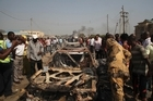 Onlookers stand by a destroyed car at the site of a bomb blast at St. Theresa Catholic Church, claimed by Boko Haram. Photo / AP
