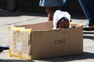 A mother and her daughter walk past a baby playing in a box in Harare. There are signs of looming elections. Photo / AP