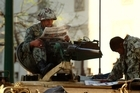 Egyptian army soldiers read newspapers as they sit atop their armored vehicles in Cairo, Egypt. Photo / AP