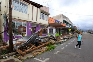 A woman crosses a street and walks past debris in Tully. Photo / AP