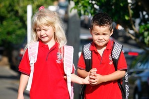 5-year-old new entrants Tiffany Thompson (L) and Caleb Woodley hold hands as they walk to Kohimarama School in Auckland. Photo / Sarah Ivey