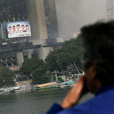 An Egyptian man looks out onto a burning government building from a bridge in central Cairo. Photo / Getty Images