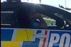 Footage of a police officer caught talking on a mobile phone while driving earlier this year.