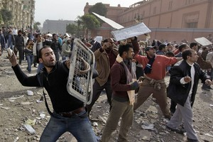 Anti-government protesters throw stones during clashes in Cairo, Egypt. Photo / AP