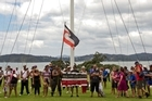 Rueben Taipari holds the tino rangatiratanga flag under the flagpole as a hikoi makes its way around the treaty grounds. Photo / NZPA