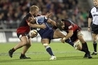 Serge Lilo of the Blues is tackled by George Whitelock and Owen Franks of the Crusaders. Photo / Getty Images