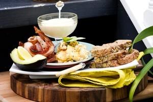 Tofu eggs with herbs, bacon, avocado and hollandaise. Photo / Babiche Martens