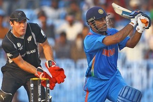 MS Dhoni of India hits the ball towards the boundary as Jamie How looks on. Photo / Getty Images