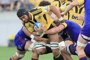 Victor Vito of the Hurricanes is tackled by Adam Thompson of the Highlanders. Photo / Getty Images