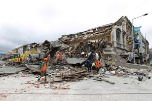 Rescue workers search for survivors through the debris. Photo / Getty Images