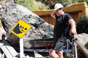 Ed Langston stands beside the large boulder that sits upon his boat at his house in Redcliffs, southeast of Christchurch, after the 6.3 earthquake. Photo / NZPA