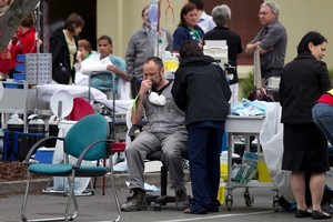 Injured residents are tended to in the carpark of a 24 hour surgery on Bealey Ave in Christchurch after the 6.3 earthquake. Photo / Simon Baker