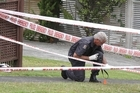 Police examinations of the yard of the Graham Place house focused on an area of grass by the front door. Photo / sunlive.co.nz