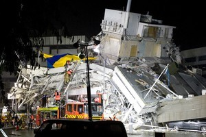 Rescue workers climb onto wreckage in central Christchurch. Photo / Mark Mitchell