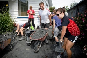Crusaders player Kieran Read helps with the clean up in the Christchurch suburb of Shirley. Photo / Dean Purcell