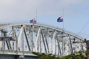 Flags fly at half mast on the Auckland Harbour Bridge, in memory of those that died in the Christchurch Earthquake. Photo / Paul Estcourt