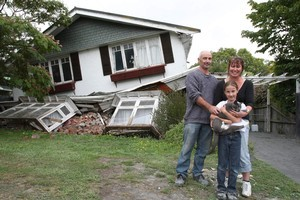 Norm Butcher, wife Maree, daughter Jasmine, 10, and Cleo the cat in front of their wrecked home. Photo / Greg Bowker