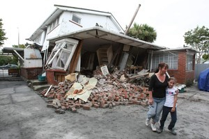 Maree Butcher with her daughter Jasmine, 10, at the back of their destroyed home in Avonside, Christchurch. Photo / Greg Bowker